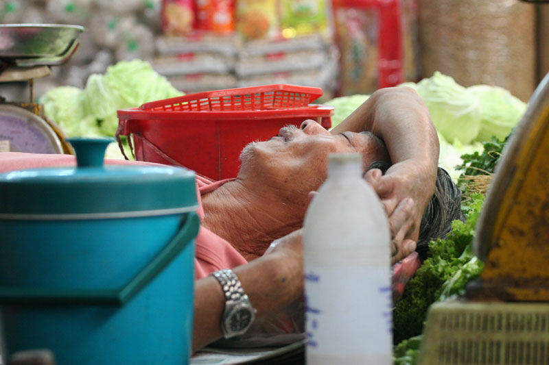 In the big market in the centre of the city of Korat, this vendor catches up on sleep.