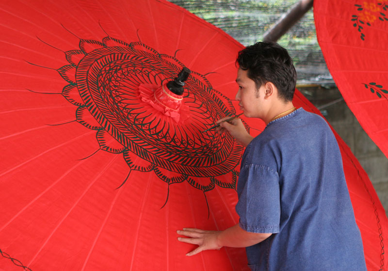 A workman paints designs on an umbrella ay a factory on the outskirts of Chiang Mai. I doubt that these are ever actually used as umbrellas as such, but more likely as decorations. Still, they look great.