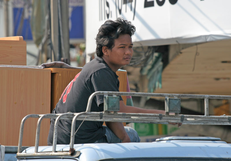 A removal man sits on the stop of the removal van. Riding atop vehicles is a common sight in Thailand.