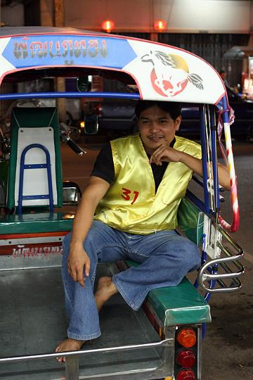 A motorcylce rider impersonates a tuktuk driver in downtown Udon Thani.