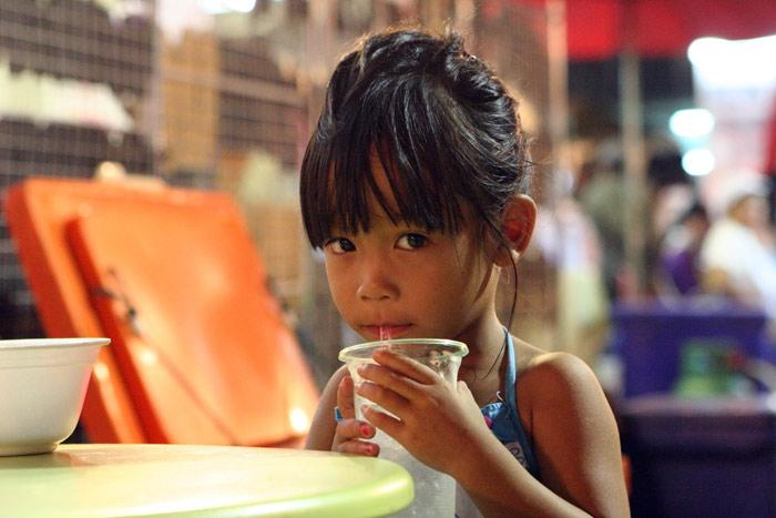 This little lady was enjoying a sweet drink at the night market in the city of Udon Thani.
