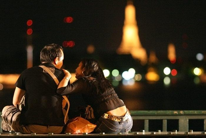 A young couple sit on Saphan Poot and look out over the Chao Praya River towards Wat Arun. The market at Saphan Poot is a popular spot for young lovers in the evening.