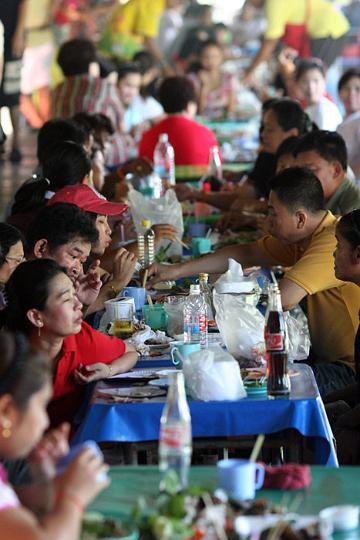 Despite not knowing each other, all of these Thais sit down and share tables while enjoying the food at a local market.
