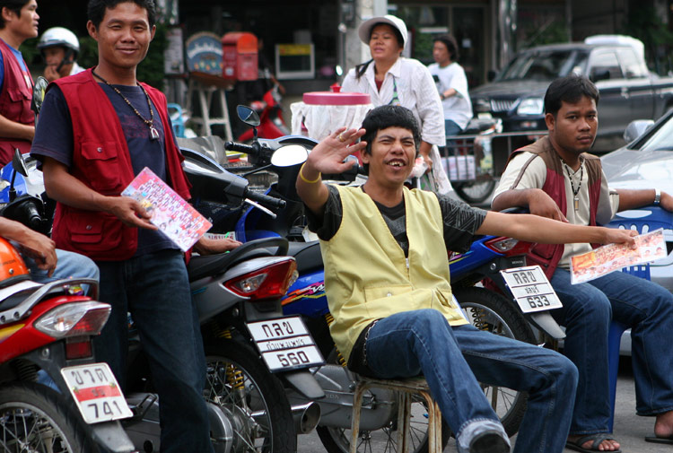 The motorbike boys at the stop of Soi Pattayaland 2. Acouple of them are holding laminated cards for the local massage parlours.