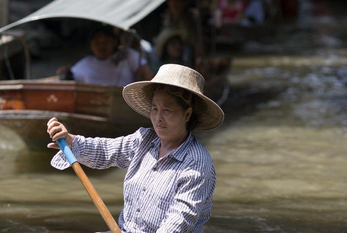 At the Floating Market at Damonen Saduak in Rachaburi, older ladies gracefully paddle their boats through the network of klongs (canals).