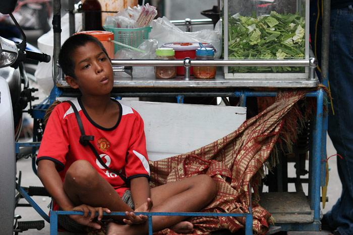 A young lad is attached to his mother's mobile kitchen on Soi 6 in Pattaya.