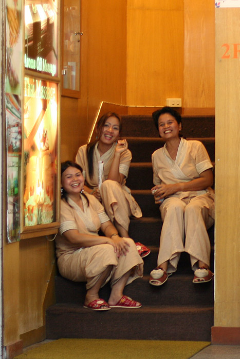 On Soi Thaniya, three Thai ladies invite passers by in for a massage.