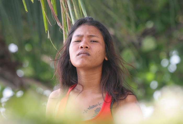A pretty, but somewhat hard-looking lass peaks over the vegetation at me on the Beach Road in Pattaya. Tattoos always make me think that a girl is tough, especially Thai women who are not so hot on tattoos, generally.