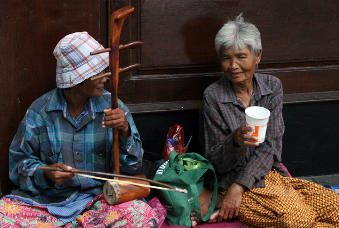 An elderly couple play Thai instruments outside the Irish Xchange on Soi Convent.