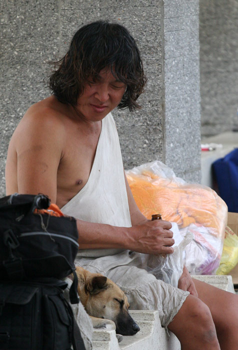 A homeless man bothers his dog which is trying to get some zzzzz. Or maybe he is asking the dog if it wants a swig of his Singha?