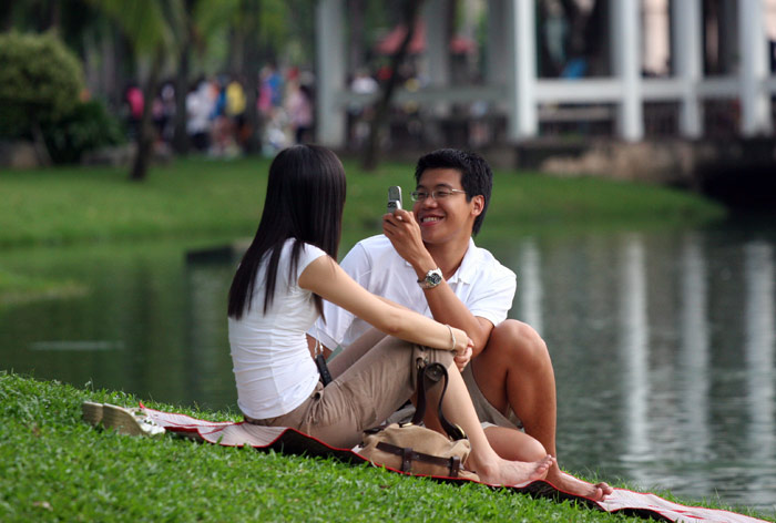 A cute couple take photographs of each other with the phone on their mobile camera at Lumpini Park.