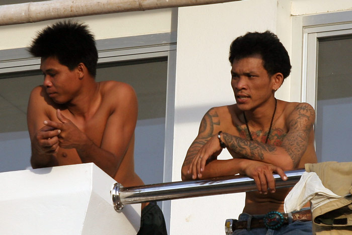 A couple of Thai labourers look like they have have just woken up for the day.