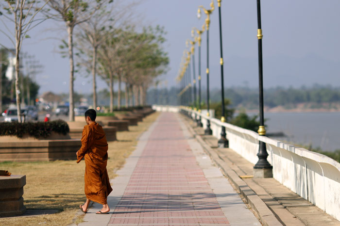 A monk strolls along the river-front promenade in pretty Nakhon Phanom.