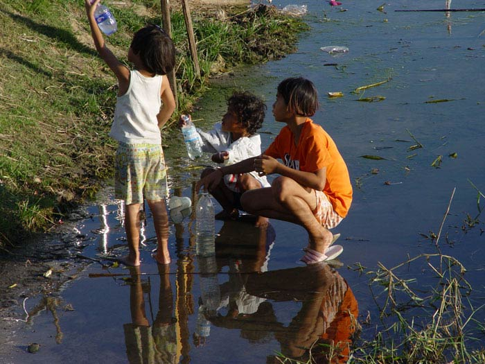 Children collecting something or other from a small lake in Korat.