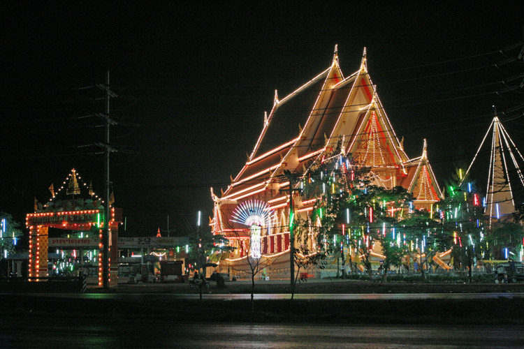 A temple just south-west of Bangkok is lit up for a festival celebrating a young guy becoming a monk.