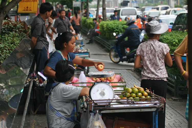 At the bottom of the stairs of the Chongnonsee BTS station, a vendor sells apples and barks out to passers by, trying to entice them to buy her product.
