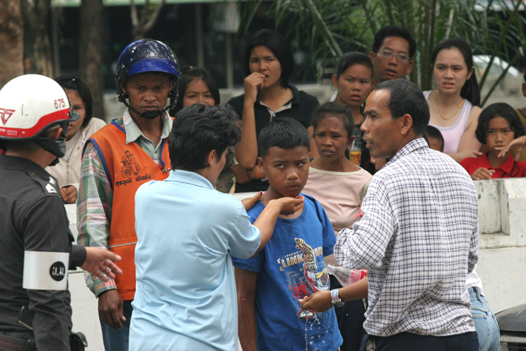 The lad in the blue T-shirt was knocked over while crossing the road by the motorcycle taxi rider, the guy in the orange vest. With cops quickly to the scene, it looked like it was not going to be cheap for him...
