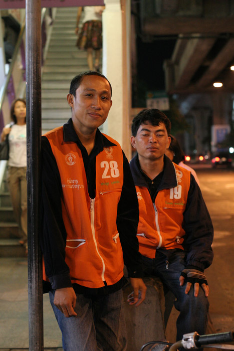 Motorcycle boys on Silom Road. The guy sitting looks out of it! Would you trust him to get you home safely?!