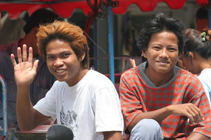 Two young Thai lads smile at the farang with he camera.