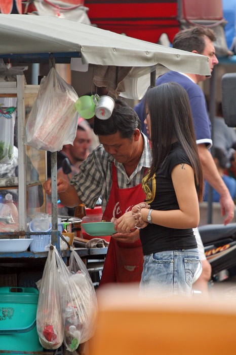 Buying a snack from a street vendor. The street vendors in Pattaya are perhaps more used to farangs than vendors elsewhere in Thailand, reflected in the fact that many have signs up in English.