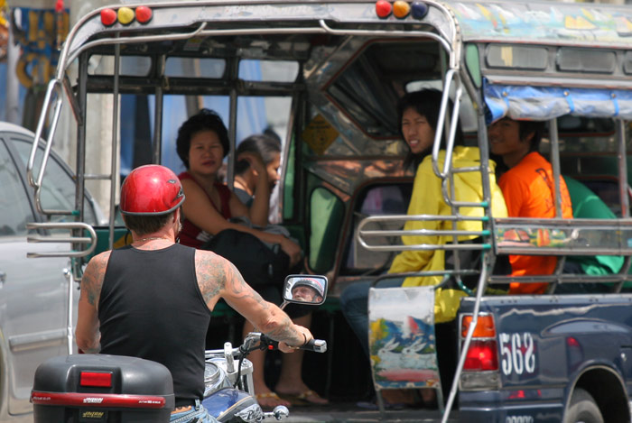 A big farang on a big bike is about to overtake a songtaew as the passengers gawk at him